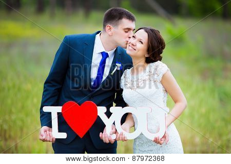 Groom kissing elegant bride on wedding day