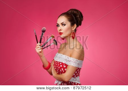 Woman with makeup brushes.   She is standing against a pink background.