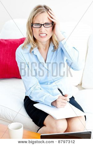 Tired Businesswoman Writing On Her Notepad Having A Headache At Home