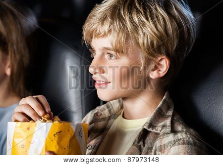 Smiling boy eating popcorn while watching movie in cinema theater