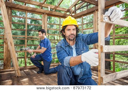 Portrait of male worker measuring wood while colleague drilling in background at construction site
