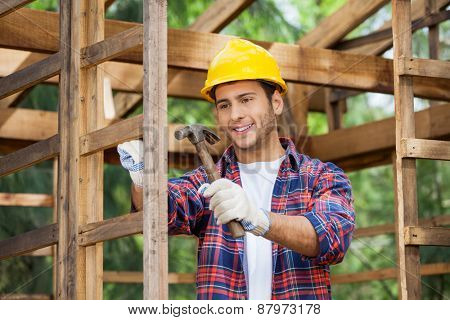 Smiling male worker hammering nail on wooden cabin at construction site