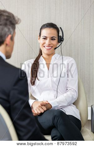 Happy female customer service agent wearing headset while looking at manager in office