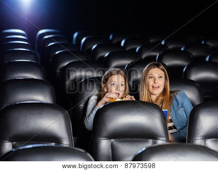 Shocked mother and daughter watching movie in cinema theater