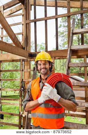 Portrait of happy male worker holding pipe in incomplete wooden cabin at construction site