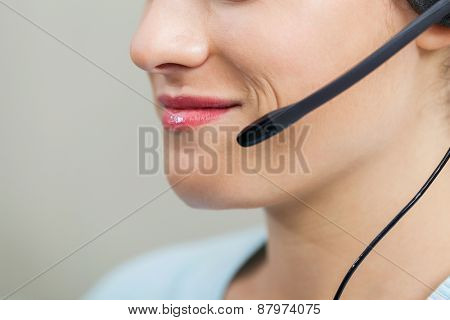 Closeup of smiling female call center employee using mic in office