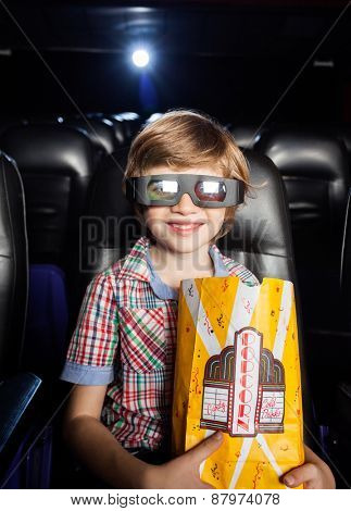 Portrait of smiling boy holding popcorn paperbag in 3D movie theater