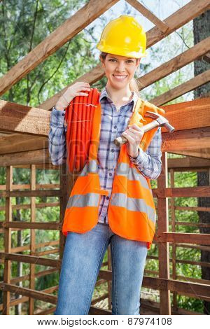 Portrait of confident female worker holding pipe and hammer in wooden cabin at construction site
