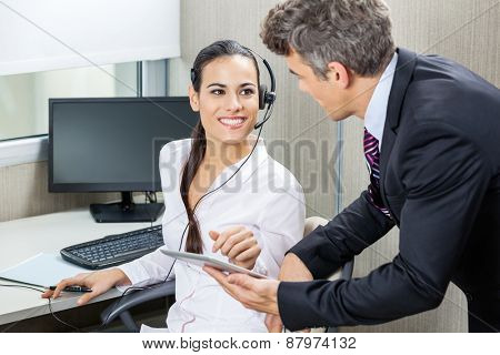 Manager and female customer service representative discussing while using tablet computer in office