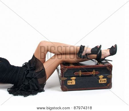 Sexy woman in little black dress keeping the legs on a vintage suitcase, isolated over white