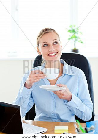 Delighted Businesswoman Drinking Coffee In Front Of Her Laptop In Her Office