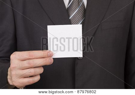 abstract man in business suit holding white card