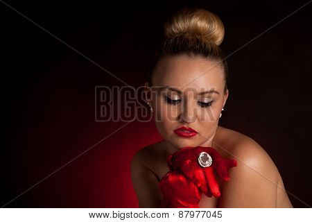 Attractive blonde woman in red gloves and a big ring