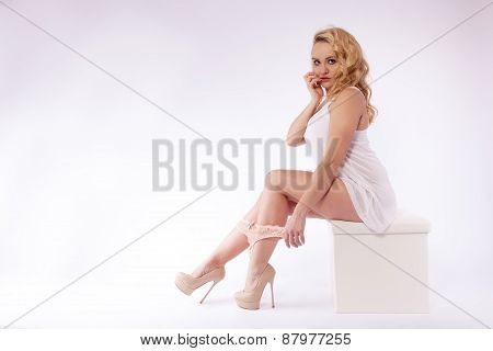 Blonde young woman in white top is sitting on a stool