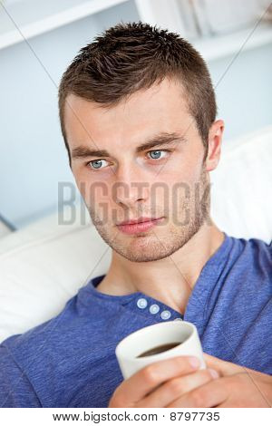Charming Caucasian Man Holding A Cup Of Coffee In The Living-room