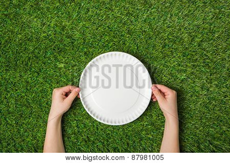 Human hands holding empty paper plate on grass