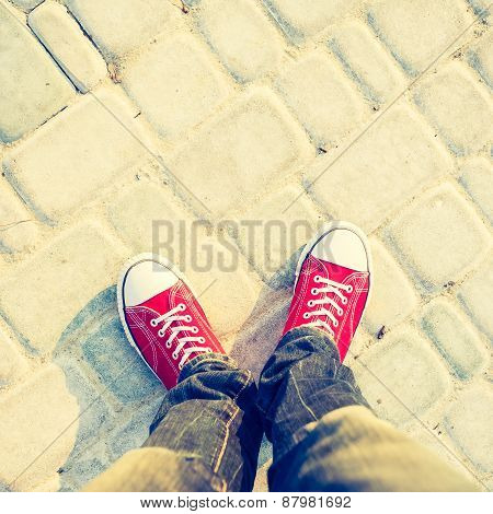 Young man feet in red sneakers on cobbled road