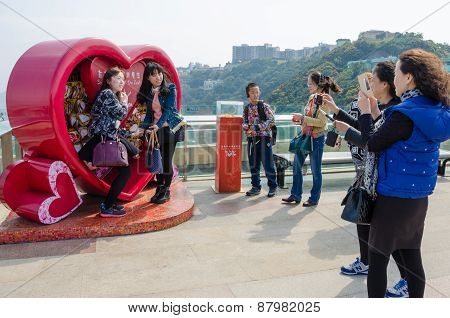Asian girls pose for photos on Victoria Peak in Hong Kong