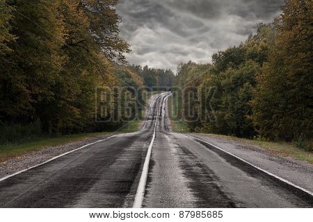 Dark asphalt road under a storm sky.