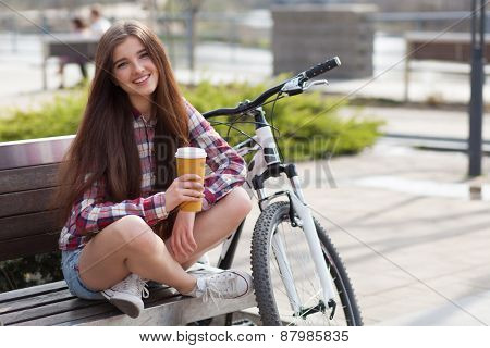 Young woman drinking coffee on a bicycle trip.