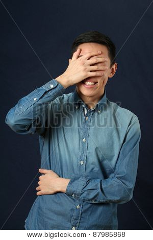 Surprised young Asian man covering his face by palm