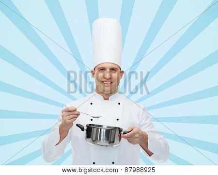 cooking, profession and people concept - happy male chef cook with pot and spoon over blue burst rays background