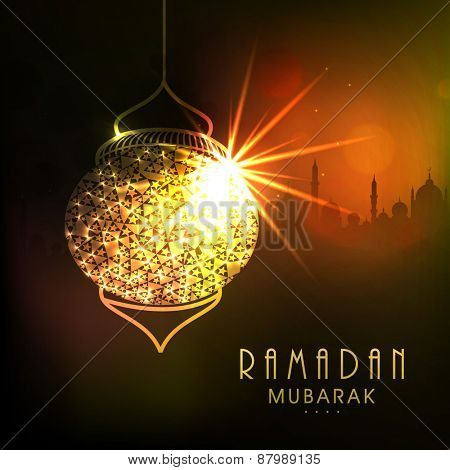 Shiny golden hanging Arabic lamp with wishing text Ramadan Mubarak on Islamic Mosque silhouette background for Muslim community festival celebration.