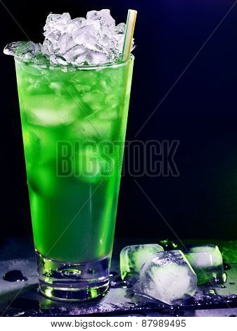 Green drink  with cube ice and mint leaf on dark background
