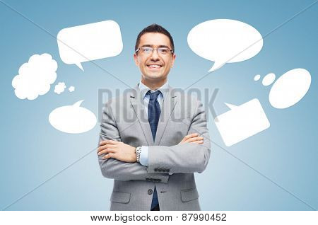 business, people and communication concept - happy smiling businessman in eyeglasses and suit over blue background with text bubbles