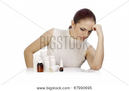Young Thoughtful Woman Looking At A Group Of Pill Bottles