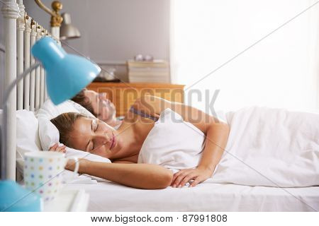 Couple Lying Asleep In Bed Together