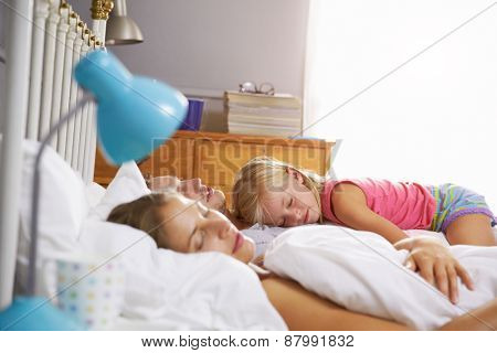 Family Lying Asleep In Bed Together