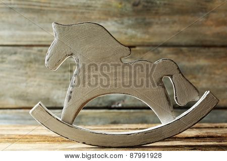 Decorative rocking horse on wooden table, close up