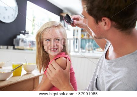 Father Brushing Daughter's Hair At Breakfast Table