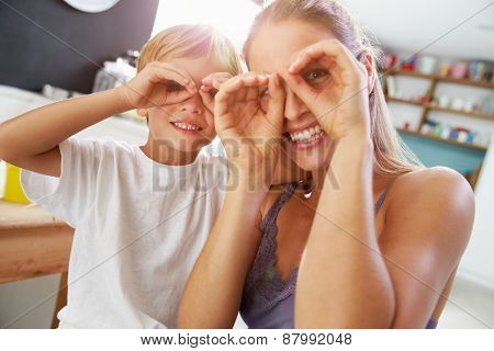 Mother And Son Making Funny Faces At Breakfast Table