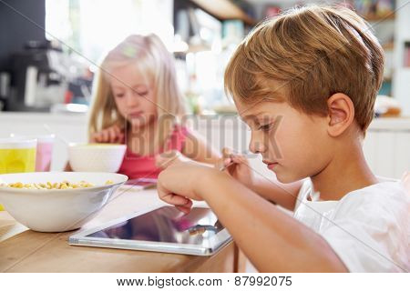 Children Eating Breakfast Whilst Using Digital Tablet
