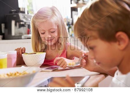 Children Eating Breakfast Whilst Playing With Mobile Phone