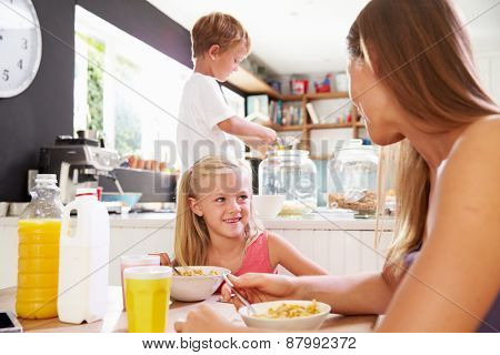 Mother And Children Having Breakfast At Kitchen Table
