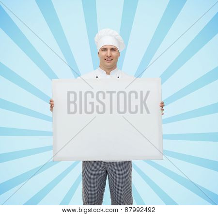cooking, profession, advertisement and people concept - happy male chef cook holding and showing white blank big board over blue burst rays background