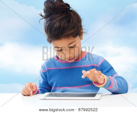 leisure, childhood, technology and people concept - little girl with tablet pc over blue sky background