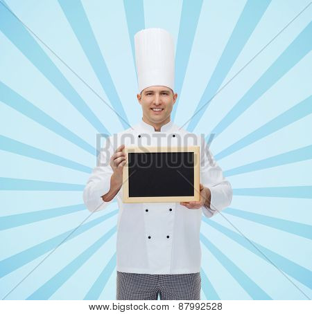 cooking, profession, advertisement and people concept - happy male chef cook showing and holding blank menu board over blue burst rays background