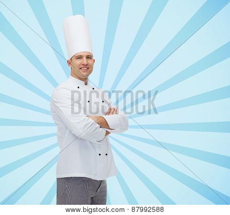 cooking, profession and people concept - happy male chef cook with crossed hands over blue burst rays background