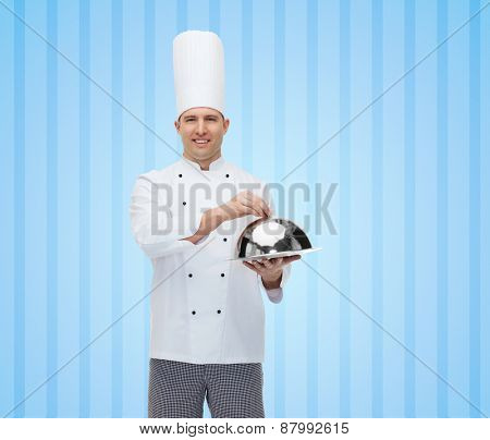 cooking, profession and people concept - happy male chef cook holding cloche over blue striped background