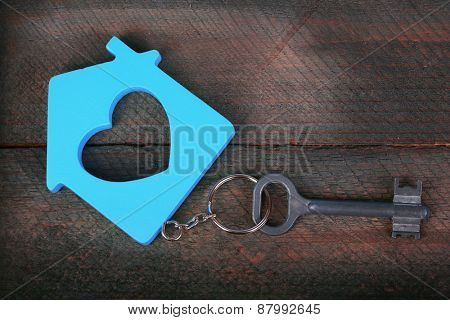 Toy house with key on wooden background