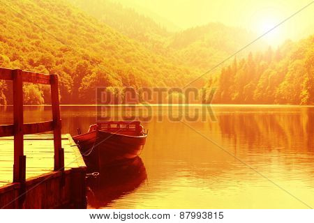 Wooden boat at pier on mountain lake