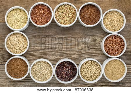 healthy, gluten free grains collection (quinoa, brown rice, millet, amaranth, teff, buckwheat, sorghum) , top view of small round bowls against rustic wood with a copy space