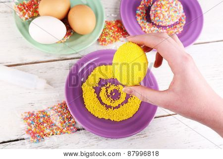 Female hand with decorated Easter egg with colorful beads on wooden table, closeup