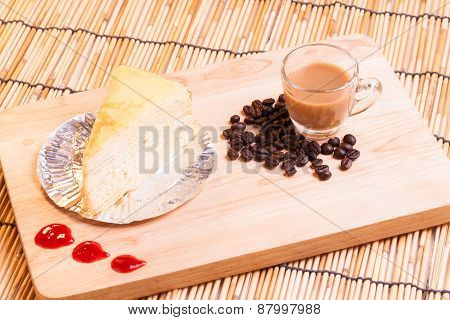 vanilla crape cake and cup of coffee on wood.