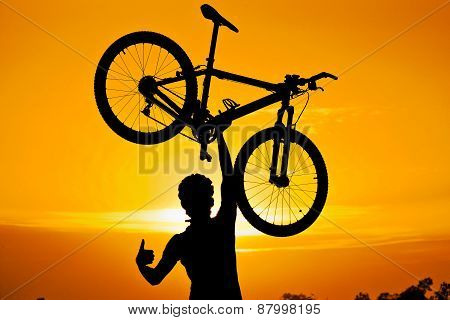 a cyclist raising his mountainbike and a trophy silhouette