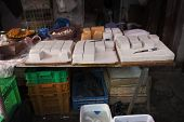 picture of curd  - Tradtional Chinese store with pieces of tofu or bean curd on display with knives on chopping boards on counter - JPG